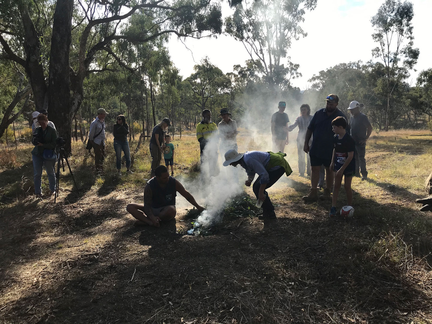 Smoke rises from a small fire tended by man sitting on the ground with people chatting and trees in the background